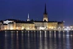 Gammal stad i Stockholm med ön Riddarholmen framtill på natten Royaltyfri Fotografi
