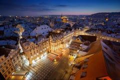 Gammal stadfyrkant i Prague med snö på tak och blå himmel under solnedgång royaltyfri fotografi