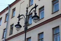 Gammal stadsgatalampa med modeller i St Petersburg, Ryssland royaltyfria bilder