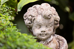Gammal staty av en begynnande ängel eller kupidon i trädgården Arkivbild