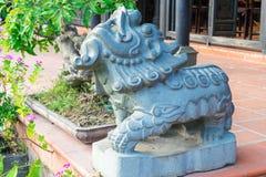 Gammal staty av stenen med blommor i asia royaltyfria foton