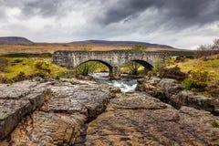 Gammal stenbro över en liten vik i de skotska högländerna royaltyfri fotografi