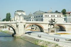 Gammal stenbro i Skopje, samman med den Karposh statyn Arkivfoto