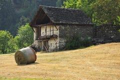 Gammal stenhus och äng i de italienska fjällängarna Royaltyfri Foto