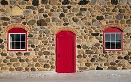 Gammal stenladugård med den ljusa röda dörren och två Windows Royaltyfri Bild