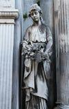 Gammal stenstatykvinna med blommor på en kyrkogård. Royaltyfri Fotografi