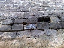 Gammal stenvägg av tuffstenar i Italien Arkivbild