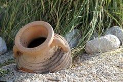 Gammal-stil grekisk amfora som lägger på jord Arkivfoton