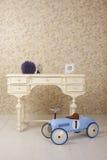 Gammal stiliserad inre med den vita tabellen och gammal blå billeksak Royaltyfria Bilder