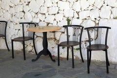 Gammal stolar och vit stenar den antika väggen i grekisk by Royaltyfria Bilder
