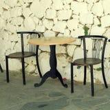 Gammal stolar och vit stenar den antika väggen i grekisk by Royaltyfri Foto