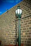 Gammal stolpe för towngatalampa med väggen och den blåa skyen Royaltyfri Bild