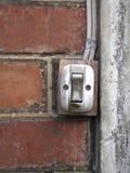 Gammal strömbrytare på tegelstenväggen Royaltyfria Foton