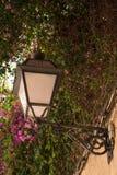 Gammal streetlamp på en vägg Arkivfoto