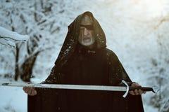 Gammal svart med huva man med svärdet arkivfoton