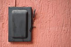 Gammal svart strömbrytare - spak över den röda väggen Royaltyfri Fotografi