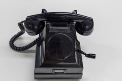 Gammal svart telefon på en vit bakgrund Arkivbilder