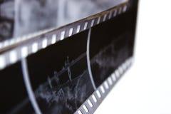 Gammal svartvit film i en spiral över vit bakgrund Gammal retro film Mycket gammal svartvit film Royaltyfria Bilder