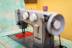 Gammal symaskin med en spole av karmosinröda trådar Arkivfoto