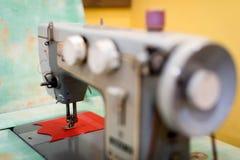 Gammal symaskin med en spole av karmosinröda trådar Royaltyfri Bild