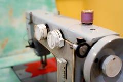 Gammal symaskin med en spole av karmosinröda trådar Fotografering för Bildbyråer