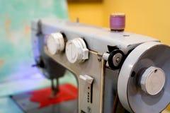 Gammal symaskin med en spole av karmosinröda trådar Royaltyfri Foto