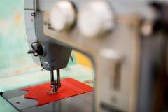 Gammal symaskin med en spole av karmosinröda trådar Arkivfoton