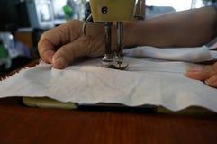 Gammal symaskin som syr torkduken med handen bakom Arkivfoton