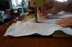 Gammal symaskin som syr torkduken med handen bakom Fotografering för Bildbyråer