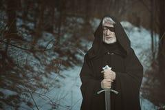 Gammal synade mannen med svärdet i mörk skog Arkivfoto