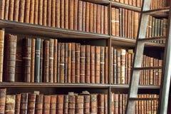 Gammal tappning bokar på den wood bokhyllan och stegen i ett arkiv Arkivbilder
