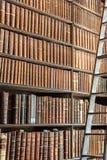 Gammal tappning bokar på den wood bokhyllan och stegen i ett arkiv Arkivbild