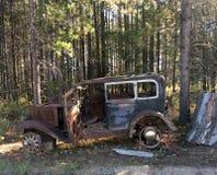 Gammal tappning Rusty Car i skogsbevuxet område i Kanada fotografering för bildbyråer