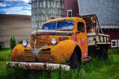 Gammal tappning skrotade lastbilen framme av en röd ladugård Royaltyfria Bilder