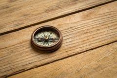 Gammal tappningkompass på tabellen Begrepp av loppet royaltyfria bilder
