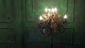 Gammal tappningljuskrona med lampor mot bakgrunden av den gröna tappningväggen arkivfilmer
