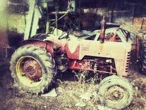 Gammal tappningtraktor som överges i för rött rostigt en åkerbruk Suffolk UK dammmaskineri för ladugård Arkivbilder