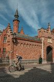 Gammal tegelstenbyggnad, blå himmel och cyklist i Bruges Arkivbild