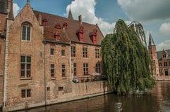 Gammal tegelstenbyggnad med folk och träd på kanalen av Bruges Royaltyfri Foto