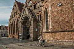Gammal tegelstenbyggnad och cyklist i Bruges Royaltyfri Fotografi