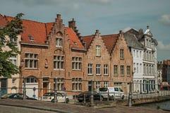 Gammal tegelstenbyggnader och bro över kanalen i Bruges Royaltyfri Foto