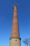 Gammal tegelstenfabrikslampglas som är hög mot den ljusa blåa himlen Royaltyfri Bild