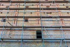 Gammal tegelstenfasad med materialet till byggnadsställning för renovering arkivbilder