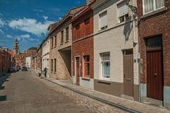 Gammal tegelstenhus och kyrktorn i gata av Bruges Arkivfoton