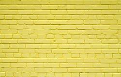 Gammal tegelstentegelstenvägg som målas med gul målarfärg för texturer eller bakgrunder Royaltyfri Fotografi