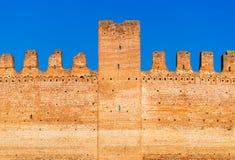 Gammal tegelstenvägg av den medeltida italienska fästningen mot den blåa himlen Fotografering för Bildbyråer