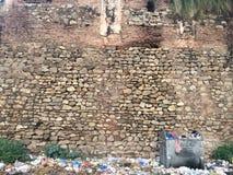Gammal tegelstenvägg med dammig slösad saker royaltyfri foto