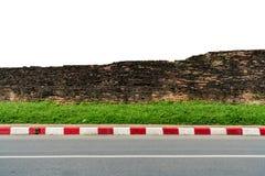 Gammal tegelstenvägg med den konkreta trottoaren Arkivfoto