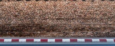 Gammal tegelstenvägg med den konkreta trottoaren Royaltyfria Bilder