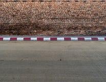 Gammal tegelstenvägg med den konkreta trottoaren Royaltyfria Foton